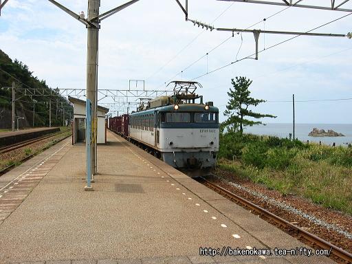 越後寒川駅を通過中のEF81形電気機関車牽引の貨物列車