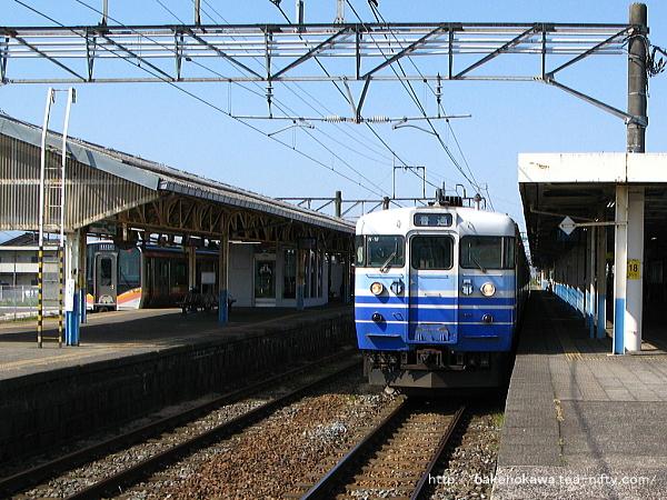 1番線に停車中の115系電車と、3番線で待機中のE129系電車