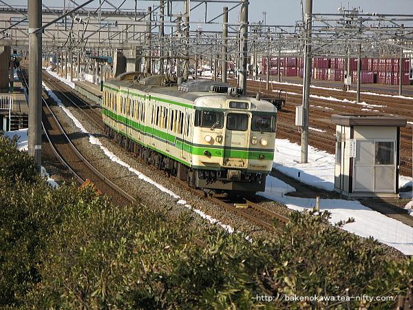 残雪の残る弥生の東新潟駅を発車加速する115系電車村上行