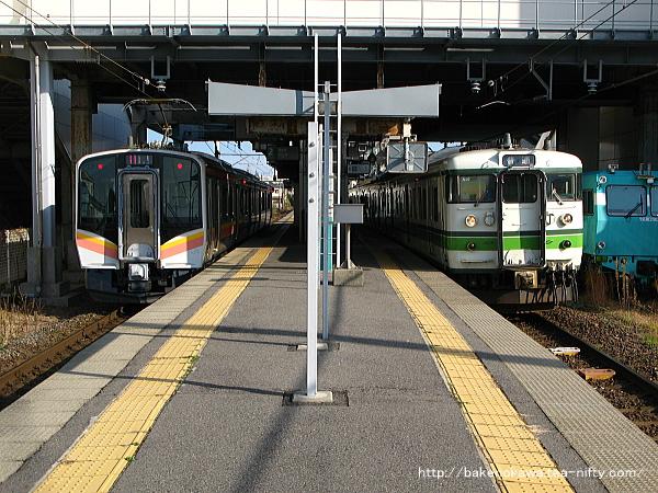 関屋駅で列車交換するE129系電車と115系電車
