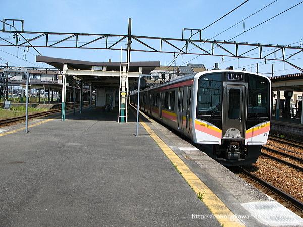 新津駅から出発するE129系電車