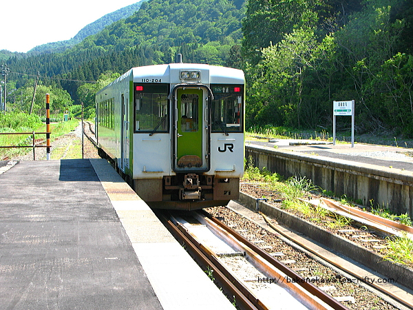棒線化した越後金丸駅を出発するキハ110系気動車米沢行
