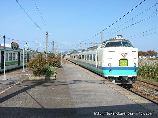 岩船町駅に停車中の115系電車と通過する特急「いなほ」