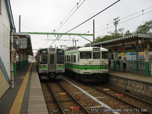 内野駅で列車交換するE127系電車と115系電車