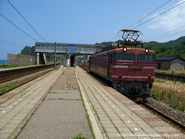 米山駅を通過するEF81形電気機関車牽引の貨物列車