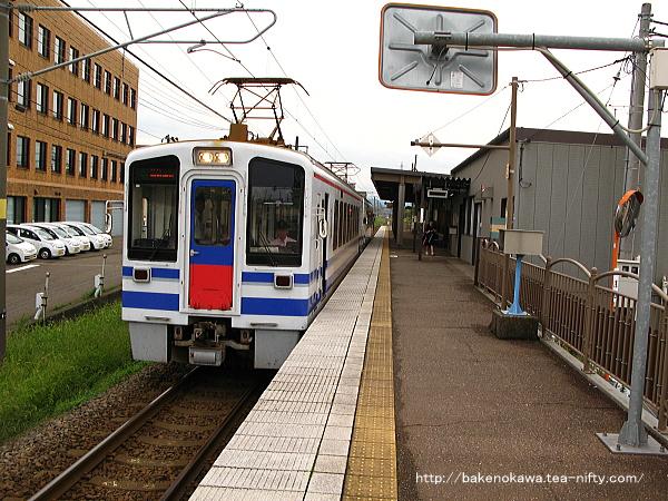 春日山駅に停車中のほくほく線直通HK100形電車