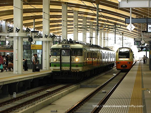 高架5番線から出発する特急「いなほ」と4番線に停車中の115系電車
